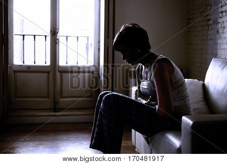 backlit silhouette of young woman holding hurting tummy suffering stomach cramp and period pain sitting on home couch in beautiful light in female menstruation concept