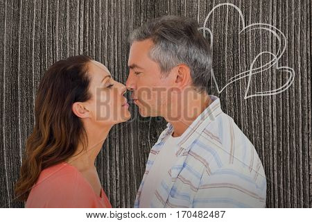 Profile view of couple about to kiss against wooden planks