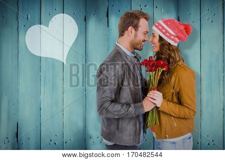 Young couple holding flowers against wooden planks