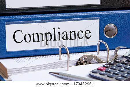 Compliance - blue binder on desk in the office