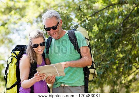 Couple smiling and looking a map on the wood