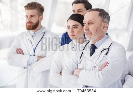 Serious medical advisers standing in apartment of clinic at conference