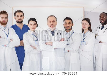 Serene group of doctors and surgeon locating in hospital apartment during meeting