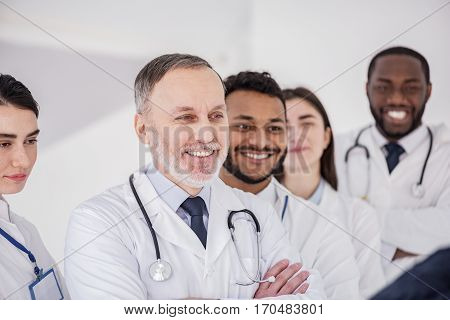 Waist up portrait of cheerful physicians situating in row at conference in hospital