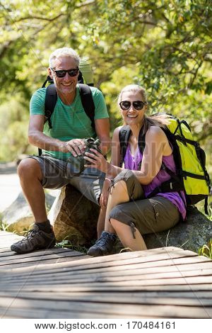 Couple smiling and taking a break during a hike on the wood