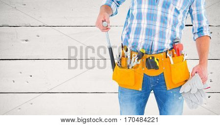 Mid section of handyman with tool belt against wooden background