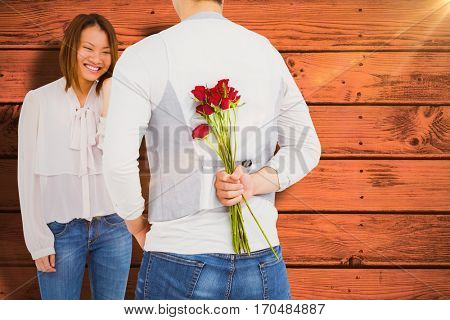 Man holding roses behind back against pink paint splashed surface