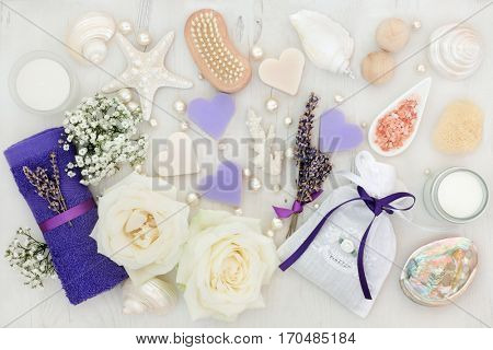 Skincare and spa beauty treatment with rose and lavender flowers, soap, moisturising cream, bath bombs and bathroom accessories with pearls and shells.