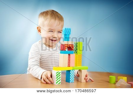 Portrait of a two years old child stacking wooden cubes. Pretty little boy on blue background