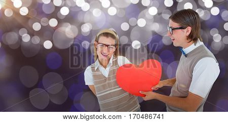 Geeky hipster offering red heart to his girlfriend against glowing background