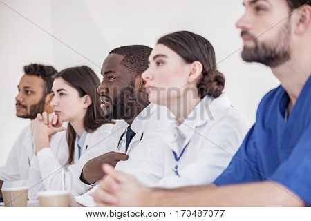 Attentive doctors listening discourse while sitting at table during meeting in white apartment of clinic