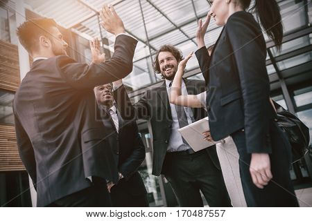 Group of happy businesspeople giving high five to each other in office premises