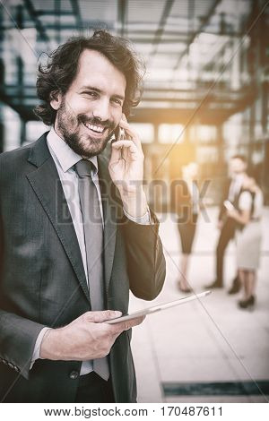 Portrait of businessman with digital tablet talking on mobile phone in office premises