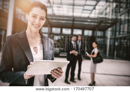 Portrait of businesswoman holding digital tablet in office premises