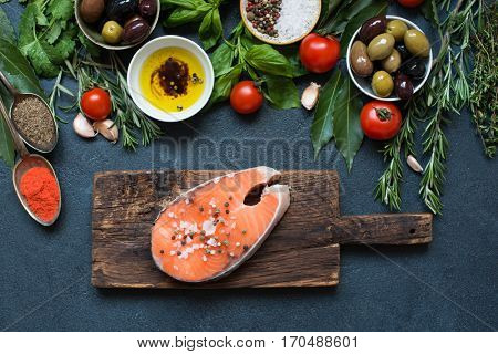 High Angle View of Fresh Raw Salmon Steaks on wooden cutting board with rosemary, spices and herbs