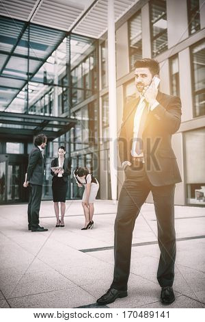 Confident businessman talking on mobile phone in office premises