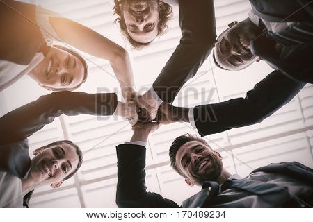 Low angle view of happy businesspeople giving high five in office premises