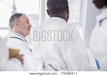 Cheerful bearded mature physician hearing lecture of affiliate during conference in bright room of hospital