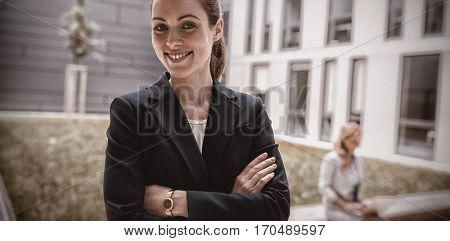 Portrait of smiling businesswoman standing in office premises
