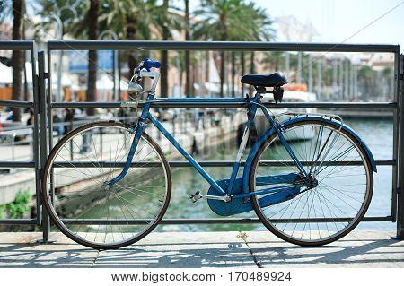 Blue bicycle near railing on a bridge over sea