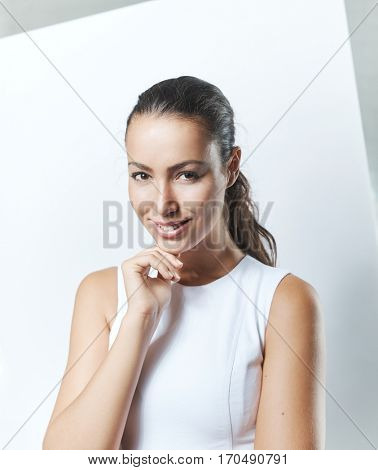 Studio portrait of happy smiling young woman, hand on chin.