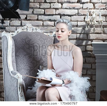 Young actress reading script before filming in retro styled interior.