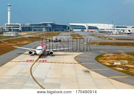Kuala Lumpur Malaysia - September 5 2015: Low cost airline Air asia aircrafts waiting for take off on the background of transit passenger terminal building in malaysian international airport KLIA 2