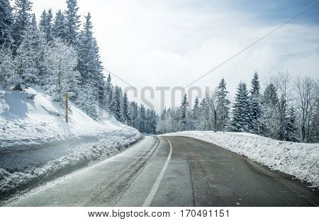Clean winter road on mountain with turns and curve with trees under the snow. Winter road with yellow marking double line and singns at winter season.