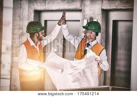 Architects holding blueprint while giving high five in office corridor