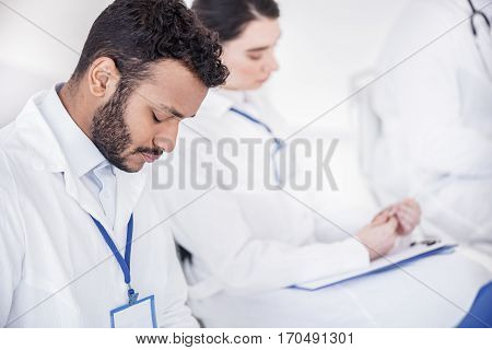 Thoughtful doctor taking notes of lecture at conference in office of clinic