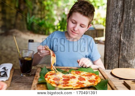 Teenage boy eating pizza for lunch