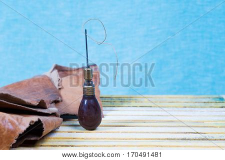 Leather craft tools on a wooden background. Leather craftmans work desk . Piece of hide and working handmade tools on a work table.