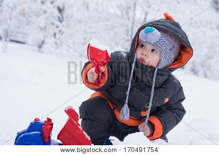 Little boy playing with snow spade and truck. Baby playing with snow in winter outdoors. Shovel snow truck. Winter vacations. Children's winter games outdoors.