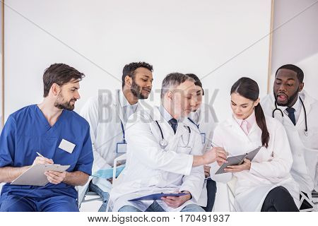 Calm old physician correcting mistakes in memorandum pad of young smiling therapeutic before meeting while sitting near his colleagues in office of clinic