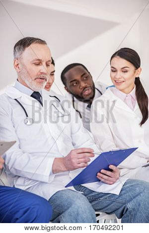 Pensive doctor reading his notes while locating near affiliates. Smiling woman watching at tablet of physician while sitting near him at conference in room of hospital
