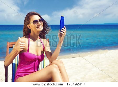 Beautiful and sexy woman in a swimsuit adding sun protection lotion. Skincare and body care concept.