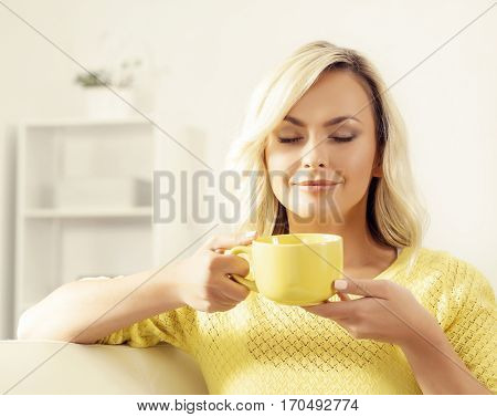 Attractive happy girl with a cup of coffee at home.