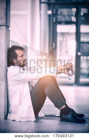 Doctor holding water bottle while sitting on floor at hospital