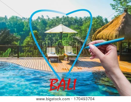The female hand with pen drawing heart and Bali background. Abstract swimming pool and love to Bali concept