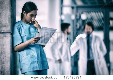 Thoughtful nurse examining medical report in hospital