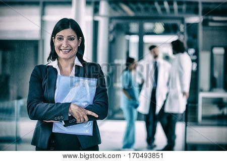 Portrait of confident businesswoman holding file in hospital