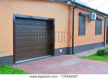 House garage door with ventilation air conditioner rain gutter pipeline system security window shutters and pavement outdoor.