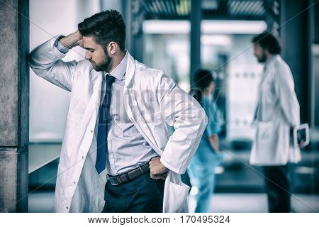 Stressed doctor standing leaning against wall in hospital