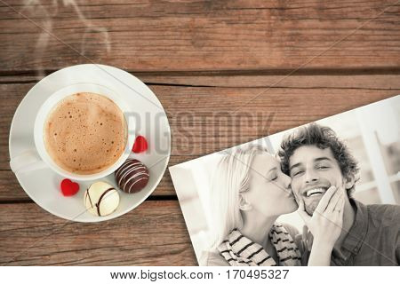 Woman kissing man on his cheek against cup of coffee