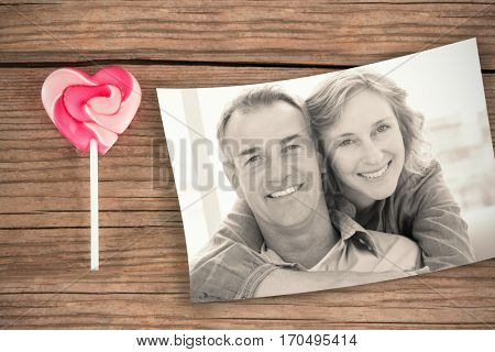 Smiling woman hugging her husband on the couch from behind against lollypop