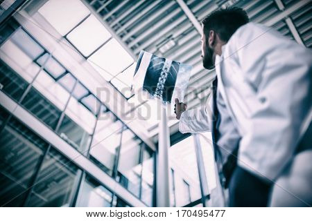Low angle view of doctor examining X-ray report in hospital