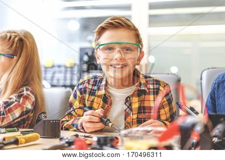 Hilarious kid is sitting near table. He holding soldering iron and looking at camera with smile
