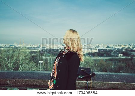 The girl with golden hair in a black coat admiring the city view
