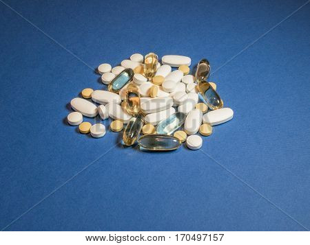 Mixed natural food supplement pills omega 3 calciummagnesium and vitamin B capsules on blue background