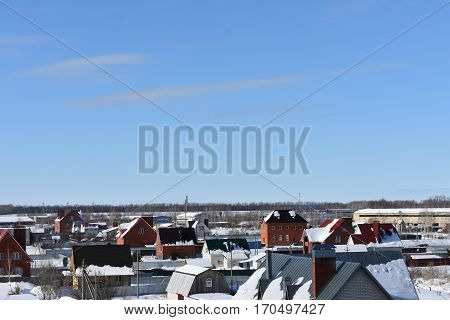 winter snowy frozen city on the background of blue sky with clouds;building, structure, facility,
